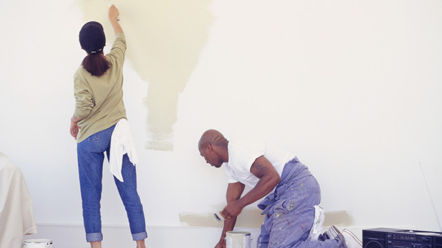 A couple painting a big wall inside