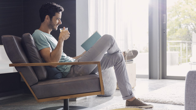 Man sitting in armchair drinking coffee reading