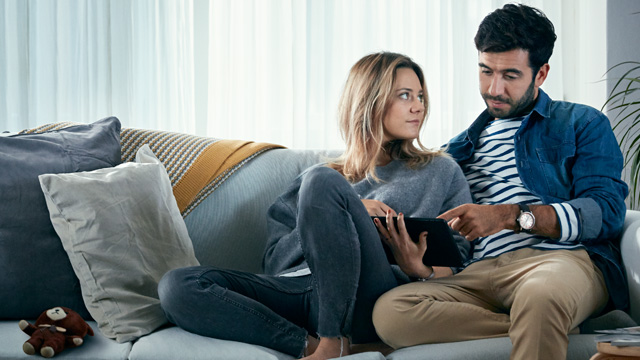 Couple sitting in sofa looking at tablet
