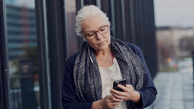Senior woman outside building with phone small