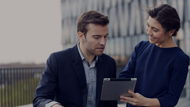 Young couple outside office building looking at tablet small