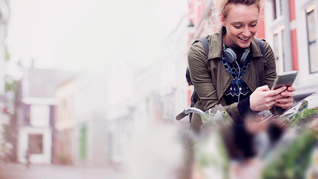 girl on bike looking at her mobile phone