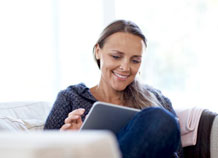 Smiling woman on a couch with a tablet